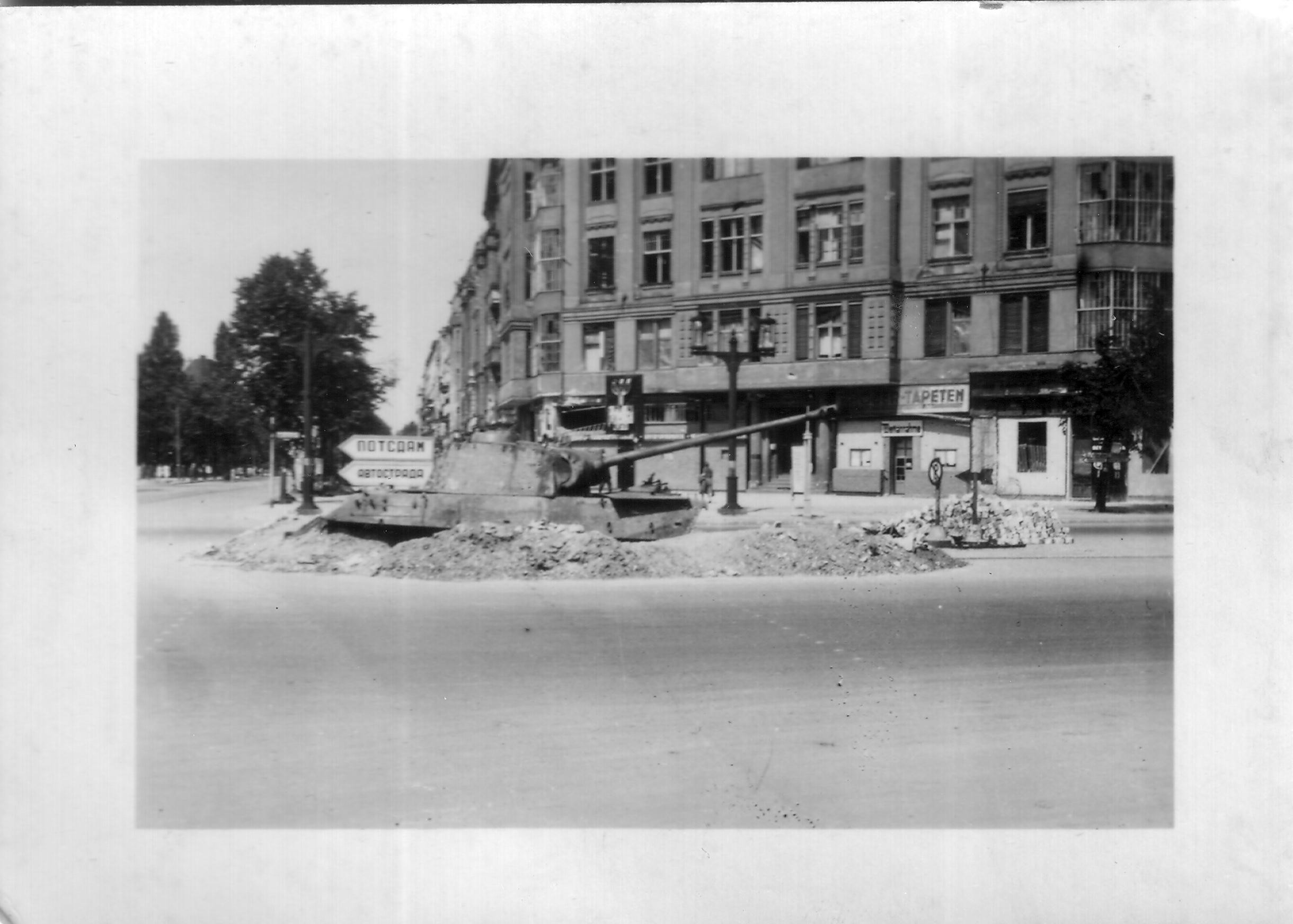 A hull down Panther tank in Berlin, with a Russian sign behind it.