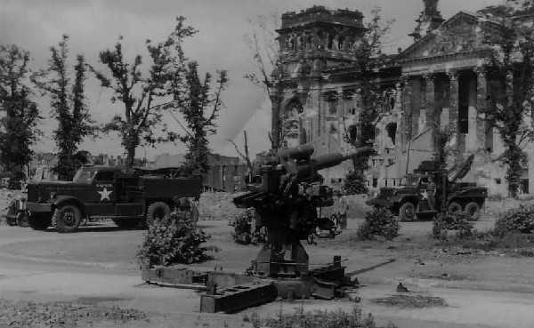 Wrecked 88mm Dual Purpose AA-A/Tk gun on the streets of Berlin with a Diamond T Tank Transporter Tractor and Scammel recovery vehicle of the 7th Armoured Division REME behind. Picture courtesy of Norman Whyte.