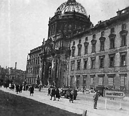 Berliners go about their dialy life in front of a major building on the ruined city,