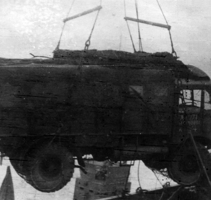 Unloading the HQ Vehicle in Normandy. The the background between the wheels there is an AA tower on a Mulberry Harbour.