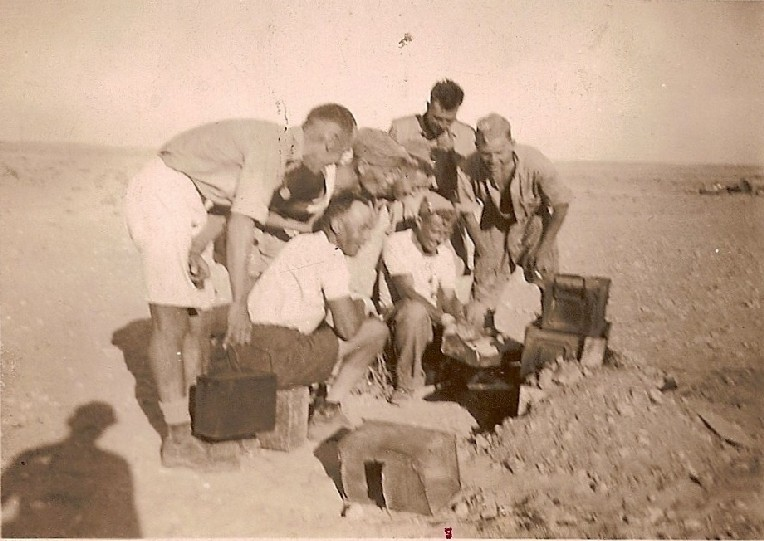 Another of the men from K Battery, 5 RHA, with an improvised oven, cooking in the desert, September 1942.  L - R: Colin Tovey (TOSKA), Arthur Rose (Mary), Harry Dormer, Jim Cromley,  Lesley Vince, Eric Smith, Bob Lerche(Jock).  Courtesy of 'Jock' (Rob) Lerche (K Bty) and Barry Forbes