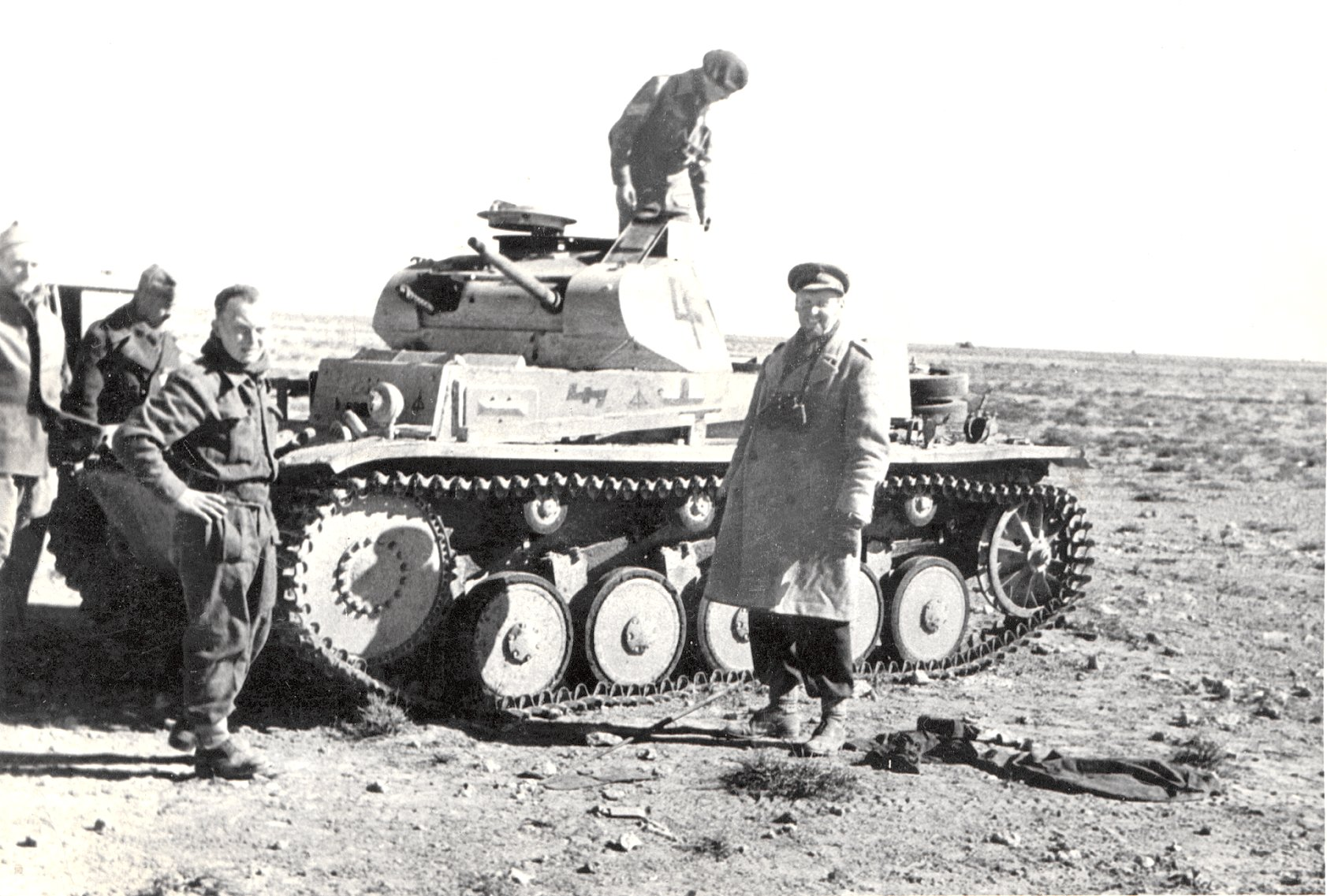 Sergeant W. Paul DuPre on top of Captured German Pz MKII Tank! On the ground:German prisoner (left), an unknown soldier, 'Slim' Hylift [later captured] and Captain Hooper [later captured]. NB The Hylift name may not be accurate as the first letter of the last name is partially obscured by old glue from photo album