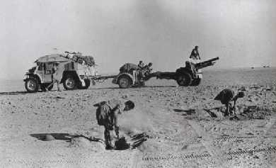Men from 4th RHA digging a gun pit, while the 25pdr Gun, Limber and Quad Tractor wait in the background.